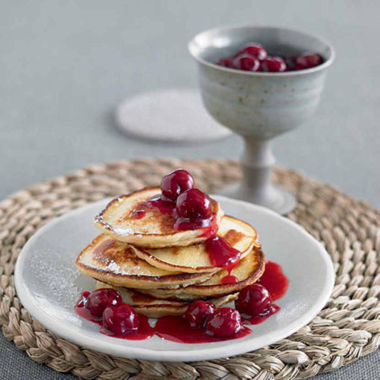 Die schmecken nach Kindheit: Unsere dicken Pfannkuchen sind dank Buttermilch so leicht, dass man sie sogar noch mit einer Kugel Vanilleeis krönen könnte.  Zum Rezept: Dicke Pfannkuchen mit Kirschkompott
