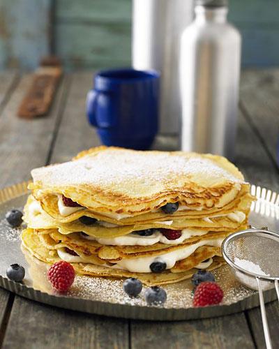 Fast zu schön zum Essen: die Pfannkuchentorte mit Beeren-Quark-Füllung und Kokosmilch im Pfannkuchenteig. Das Backen der Pfannkuchen dauert zwar ein bisschen, die Torte kann aber sehr gut vorbereitet werden. Zum Rezept: Pfannkuchentorte