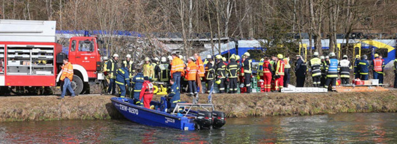 Rettungskräfte und Helfer am Unglücksort in Bayern, im Hintergrund sind die verunglückten Züge zu sehen.