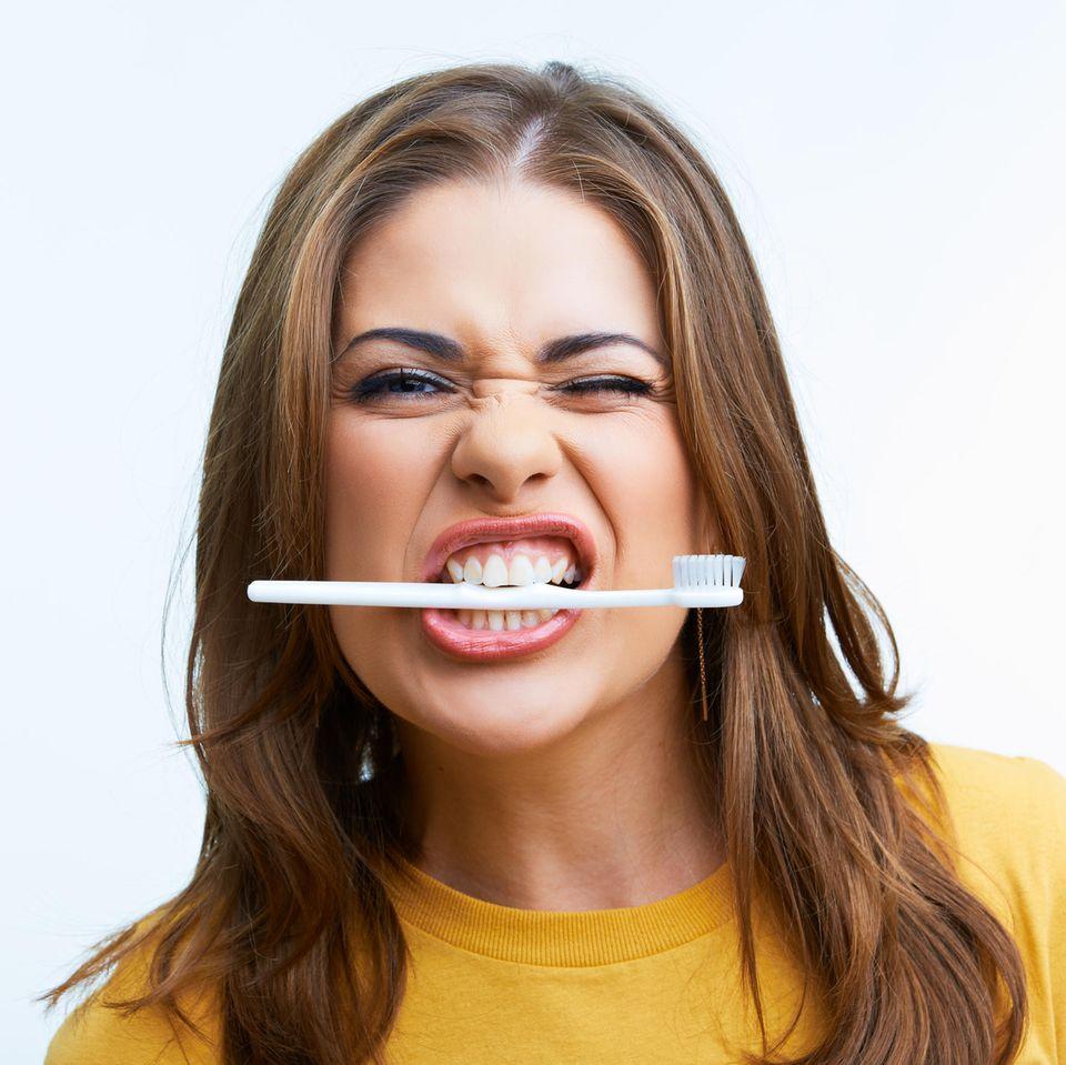 Frau mit Zahnbürste im Mund