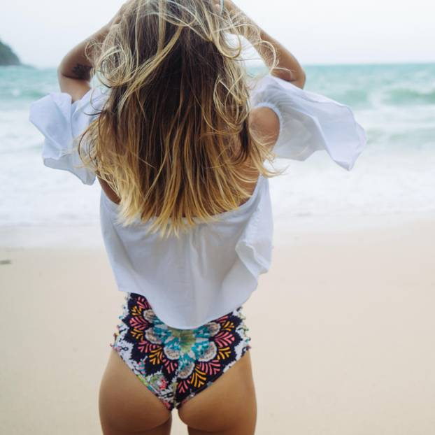 Frau trägt Bikini-Höschen und weiße Bluse