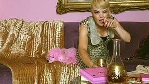 Rosa Pudel auf goldigem Untergrund. Und dazu eine wunderbar versoffene Katrin Sass