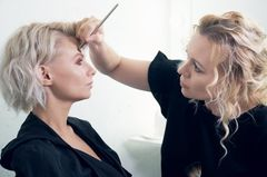 Frau bekommt Stirn geschminkt