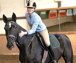 Pferdesport: Die Reiterin muss noch üben, das Pferd hat seine Sache gut gemacht. Gelobt wird mit Klopfen.