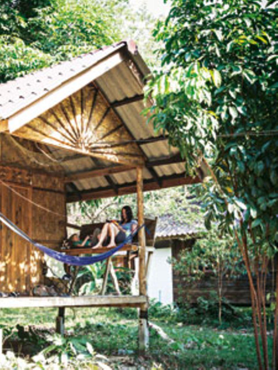 Siesta Thailandia: Während die Mittagssonne auf die Insel Koh Phayam brennt, verziehen sich Susanne und Fred zum Lesen auf ihre Veranda. Wenn die Mama Glück hat, liest der Sohn auch mal vor