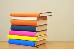 Stapel bunter Bücher auf Tisch