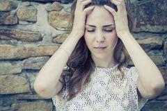 Regelschmerzen: Leidende Frau hält sich den Kopf