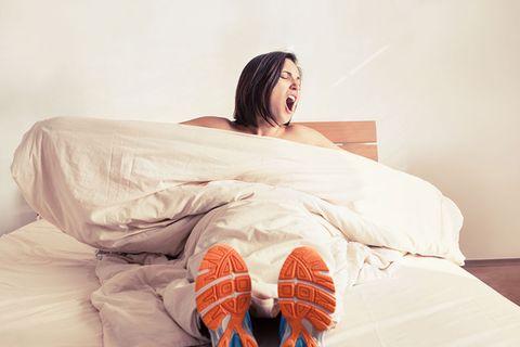 Fitnessübungen fürs Bett: Frau mit Turnschuhen liegt im Bett