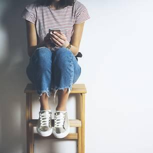 Wie wirkt sich EInsamkeit auf den Körper aus: Frau auf Stuhl