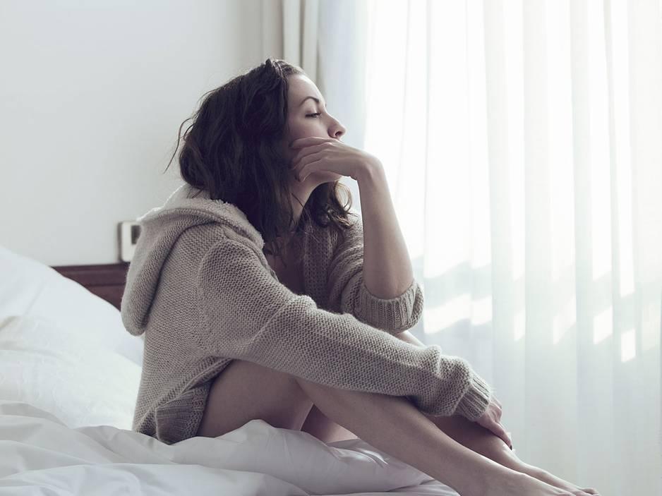 7 Gründe, warum deine Periode zu spät kommen kann: Frau sitzt auf dem Bett