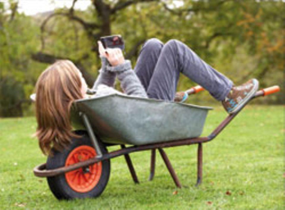 Eine Frau schreibt eine Nachricht während der Gartenarbeit