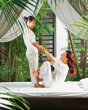 """Arme langziehen: Bei der Thai-Massage im Spa-Garten des Resorts """"Fusion Maia Da Nang"""" bringt Therapeutin Mai vollen Einsatz und klettert gleich mit auf die Liege."""