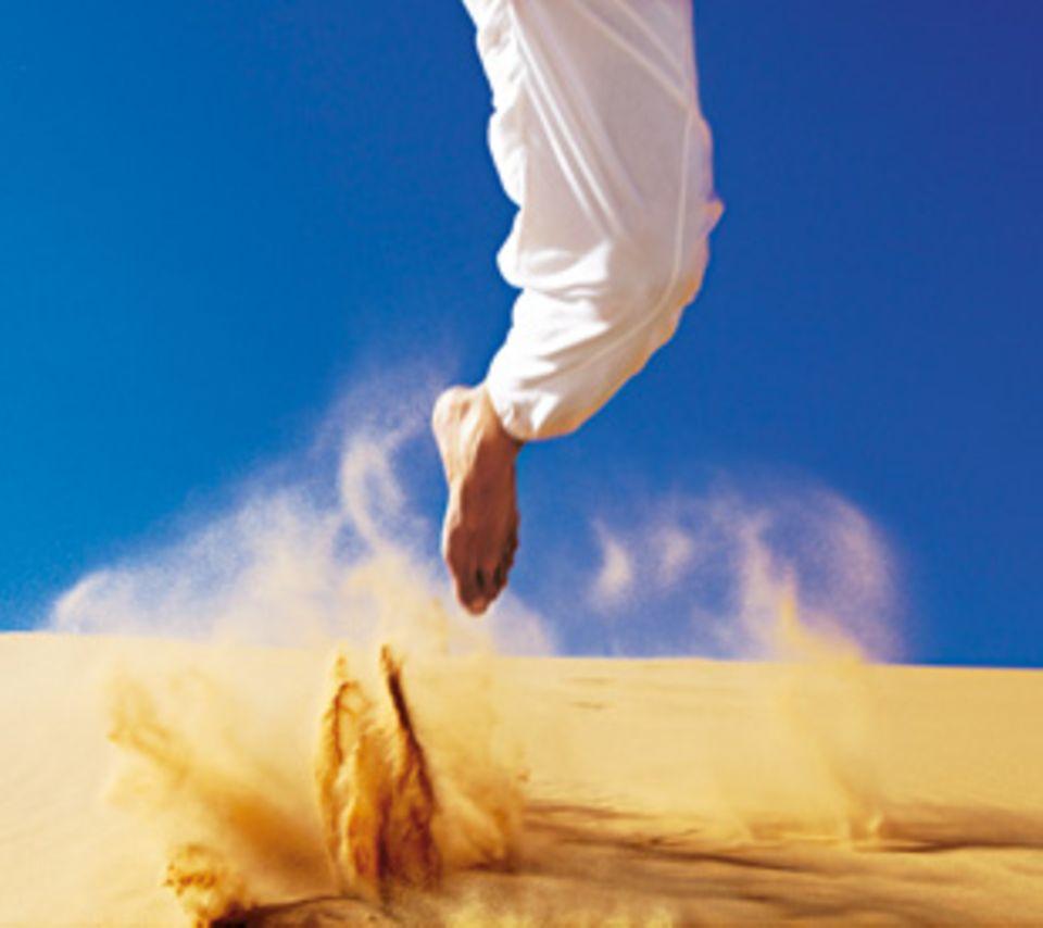 Reiseleiter M'Barek lässt den Sand spritzen.