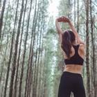 Rückenfett loswerden: Frau dehnt sich beim Sport im Wald