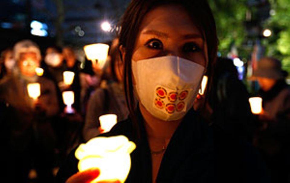 Stille Trauer: Im ganzen Land wird ein Jahr nach dem Tsunami der Opfer gedacht.