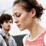 Kommunikation: Frau schaut schweigend zu Boden, Mann blickt enttäuscht zu ihr rüber