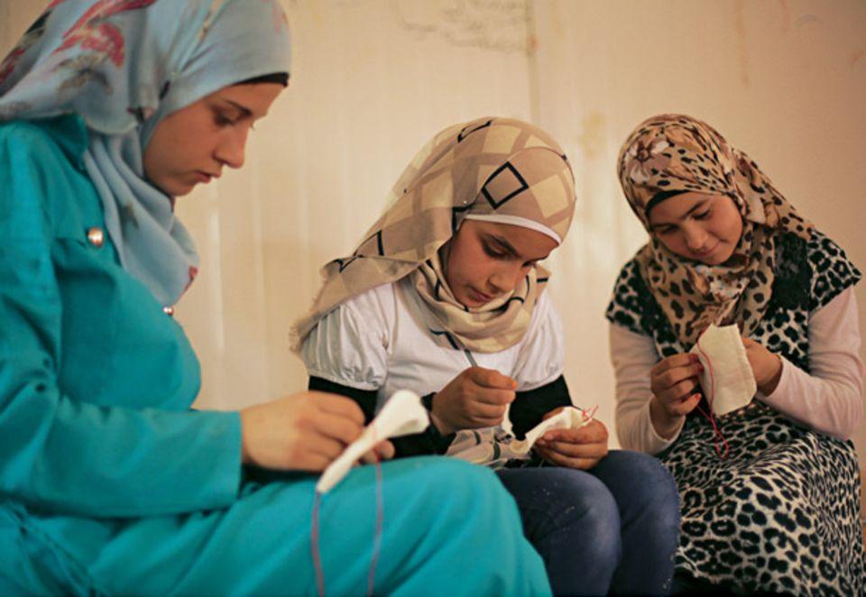 """Aya und Malak sticken im """"Child Family Center""""."""