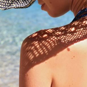 Frau mit Hut am Strand in der prallen Sonne