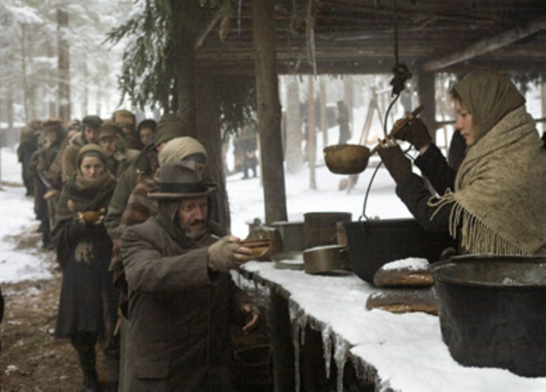 Chaya (Mia Wasikowska, mit Allan Corduner) gibt in der Suppenküche des Lagers Essen aus