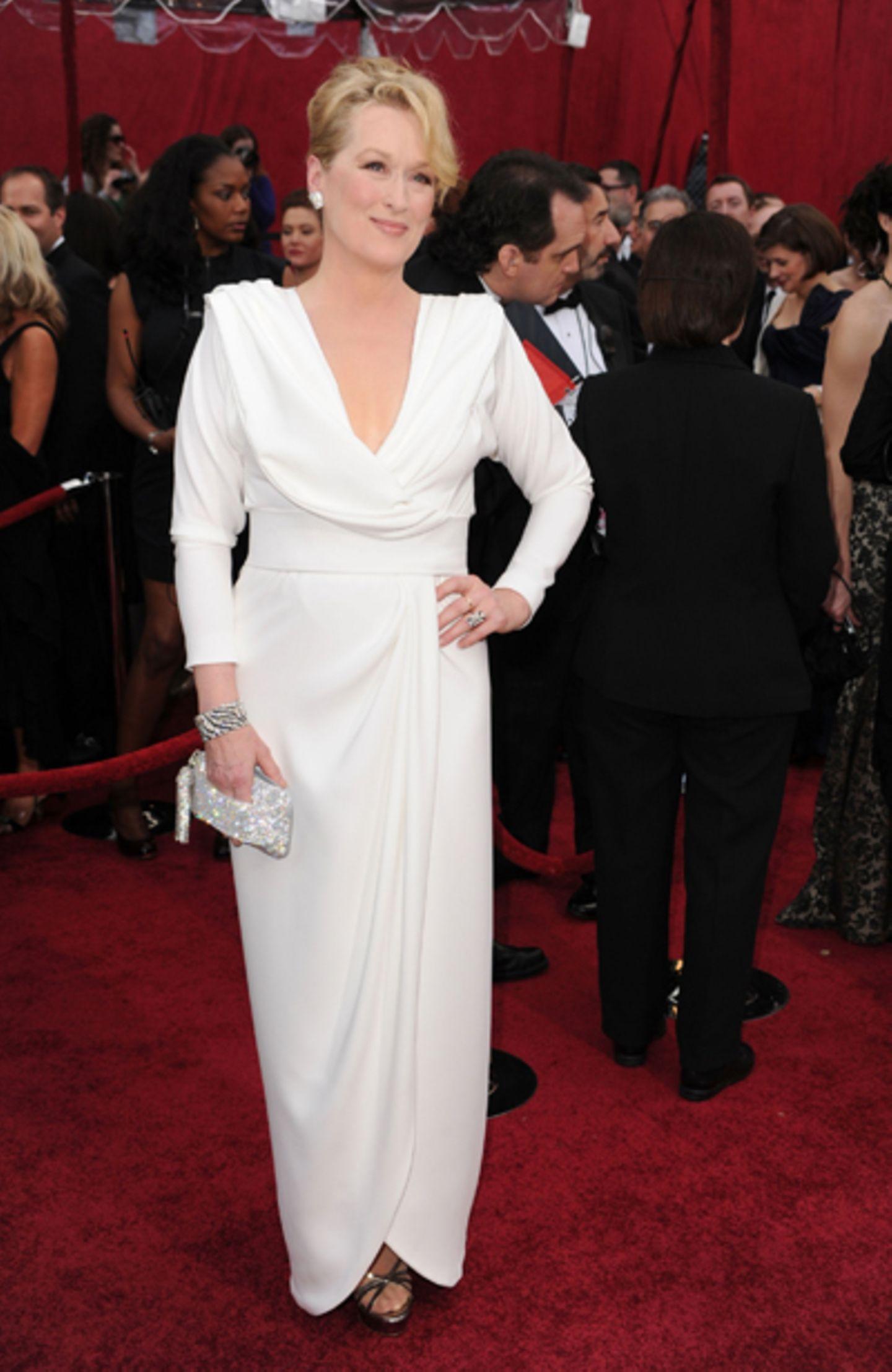 Meryl Streep Mit frisch blondierter Hochsteckfrisur und Diamantohrringen strahlte die 60-jährige zufrieden in die Kameras und bewies, dass Schönheit keine Frage des Alters ist. Und falls doch, dass wahre Ausstrahlung erst mit dem Alter kommt. Lässig schick mutete ihr weißes Kleid mit Wasserfall-Revers und langen Ärmelnan. Silberschmuck und zierliche Sandaletten dazu - fertig ist der Oscars-Look.