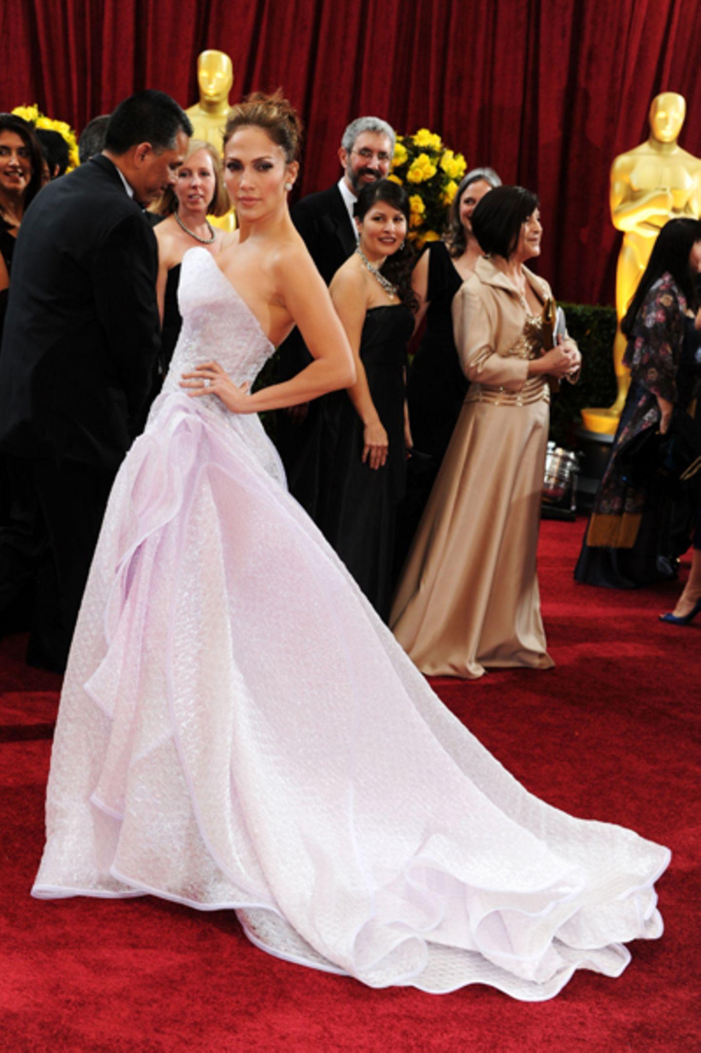 Jennifer Lopez Fast wie eine Barbie: In ihrer weißen, voluminösen und seitlich drapierten Bustierrobe mit Schimmer-Effekt sah La Lopez ein bisschen so aus, als würde sie zu ihrer eigenen Hochzeit gehen. Fehlte nur noch der Bräutigam. Unser Fazit: Zu Weiß und zu Möchtergern-Prinzessin!