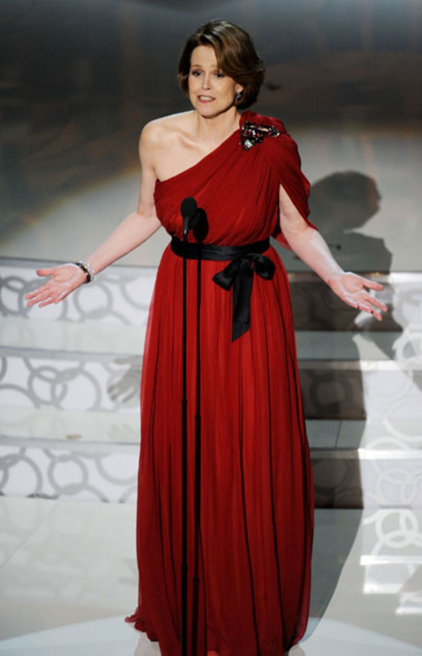 """Sigourney Weaver Der immer noch verdammt durchtrainierte """"Alien""""-Star kam in einer tomatenroten Abendrobe mit schwarzer Satin-Schleife. Zwar steht ihr der One-Shoulder-Look sehr gut, aber der Schnitt der Robe erinnert zu sehr an eine römische Toga, und außerdem beißt sich ein rotes Kleid so gut wie immer mit dem roten Teppich."""
