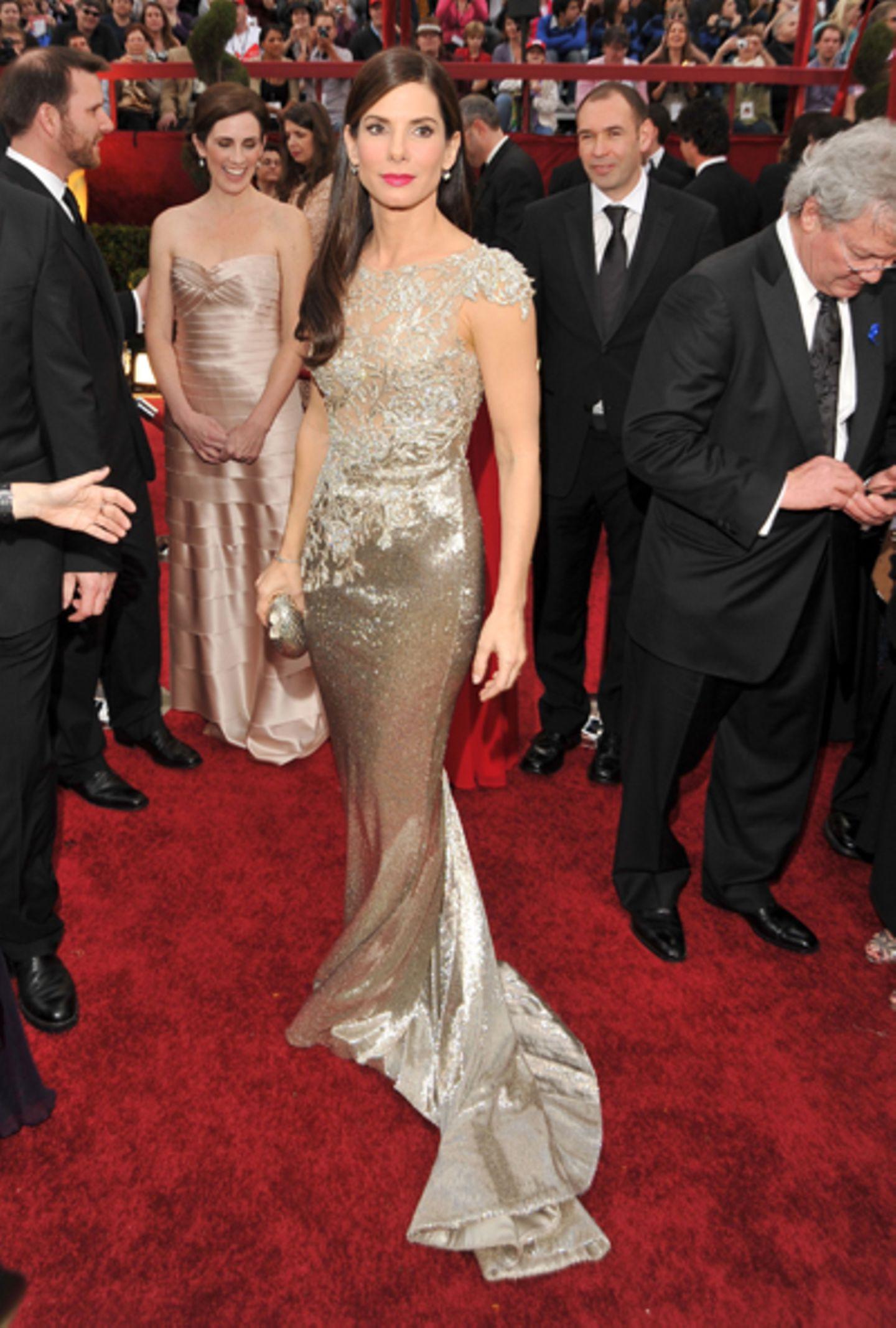 """Sandra Bullock Es war ihre erste Oscar-Nominierung, und es blieb nicht nur bei der Nominierung: Sandra Bullock gewann in der Kategorie """"Beste Hauptdarstellerin"""" für """"Blind Side - Die große Chance"""". Ihre Garderobe konnte sich auch sehen lassen. Der Star strahlte mit seiner figurbetonten Glitzer-Spitzenrobe um die Wette. Einen schönen Farbakzent setzte ihr himbeerroter Kussmund. Das Make-up hätte allerdings ein wenig frischer sein können, Sandra wirkte ziemlich blass um die Nase."""