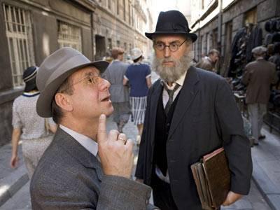 """TV-Tipp """"Marcel Reich-Ranicki: Mein Leben"""": Marcels Vater David Reich (Joachim Król) hat einen Hebräisch-Lehrer (Joachim Berger, rechts) für ihn gefunden. Auf der Straße halten sie inne, als sie Klaviermusik hören."""