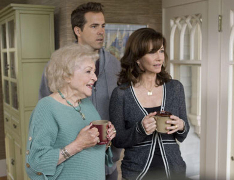 Großmutter Annie (Betty White), Mutter Grace (Mary Steenburgen) und Andrew (Ryan Reynolds) beobachten irritiert, wie Margaret mit einem Morgenmantel bekleidet und Hund unterm Arm im Garten herum rennt.