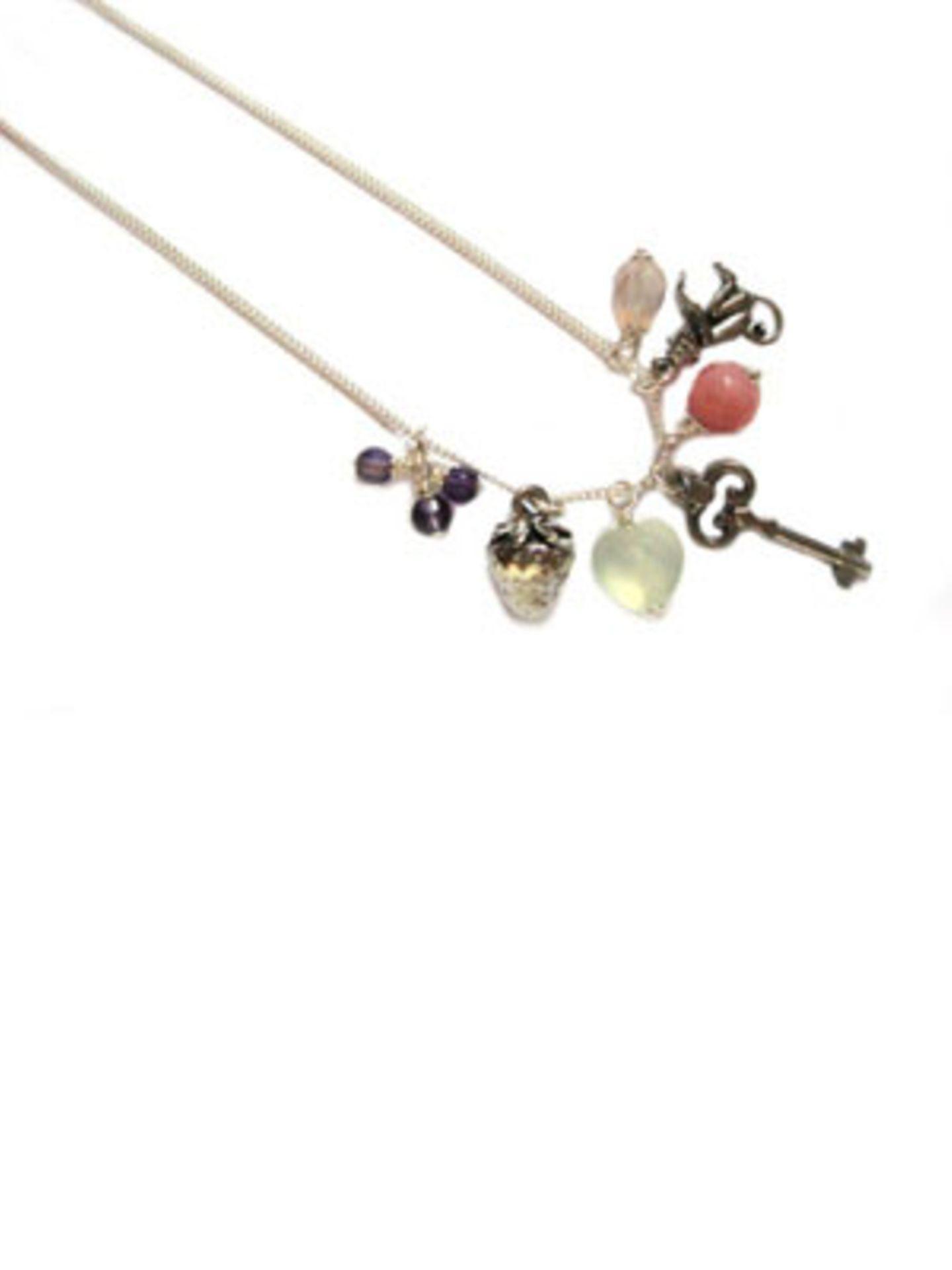 Lange Silberkette mit verschiedenen Charms, darunter ein kleiner Schlüssel und eine Erdbeere, von Daily Obsessions, um 80 Euro. Über www.dailyobsessions.com.