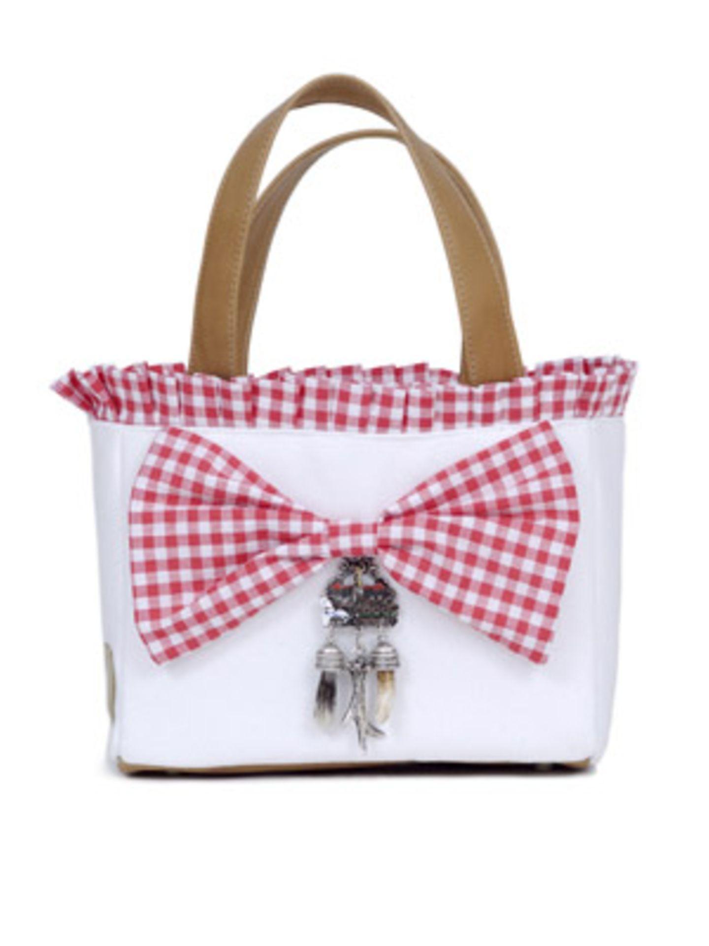 Henkeltasche in Weiß mit rot karierter Schleife und bayrischen Applikationen von Mandana Just Bags, um 110 Euro.