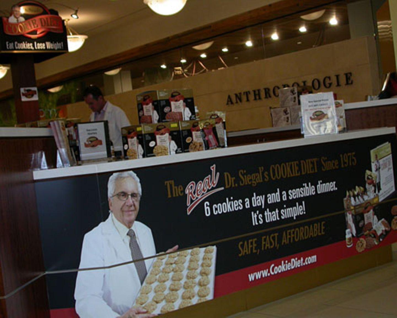 So einfach geht Abnehmen: Nur sechs Spezial-Kekse am Tag und eine vernünftige Mahlzeit. Der Miamier Arzt Dr. Siegal – hier mit einem Stand in der Aventura Mall vertreten – soll es möglich machen.