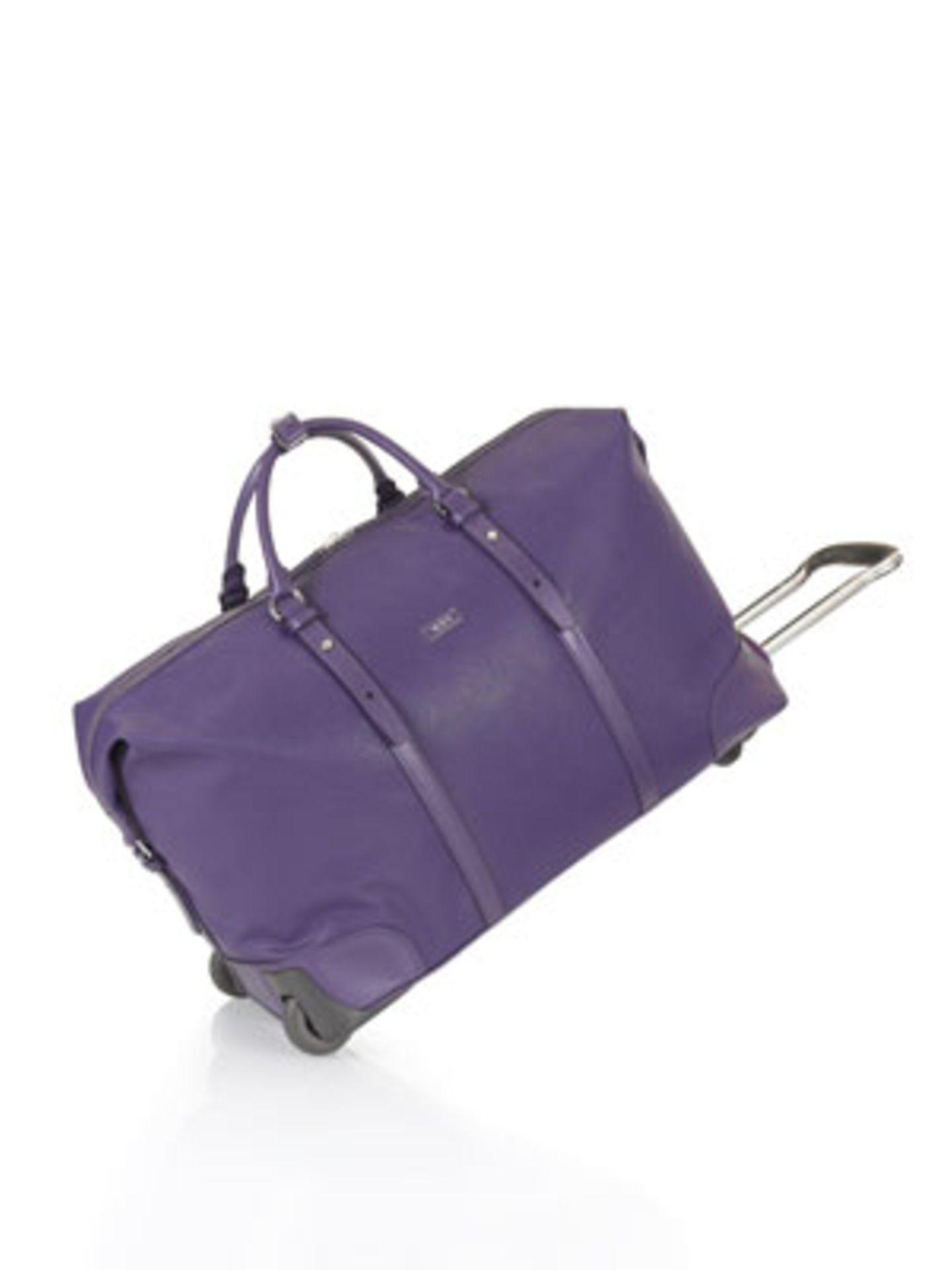 Reisetasche aus violettfarbenem Leder mit Rollen von Tumi, um 895 Euro.