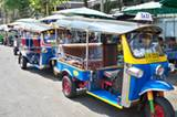 Tuk Tuk-Parade in den Straßen Bangkoks. Die Fahrer machen am Straßenrand eine Pause bei grünem Tee mit Weizengras und warten auf Kundschaft.