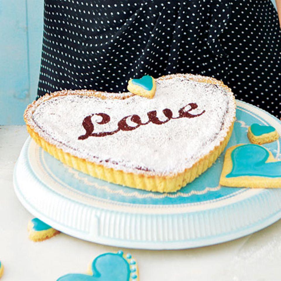 """Dieser schokoladige Kuchen ist schnell gebacken: Mit einer Herz-Tarteform und einer Love-Schablone kann er eine besondere Überraschung für deinen Liebsten werden. Zum Rezept: """"Love""""-Kuchen"""
