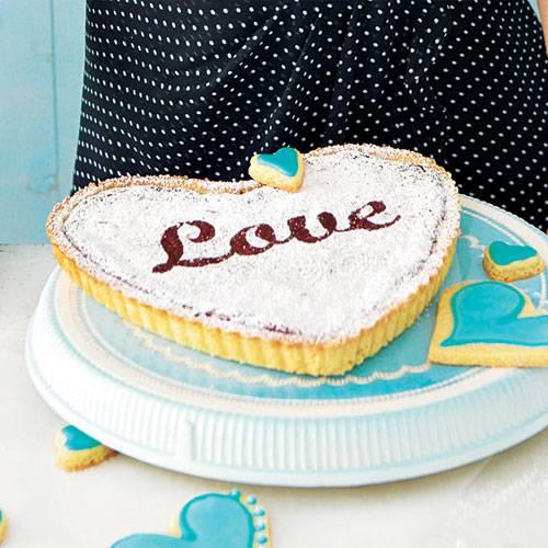 """Dieser schokoladige Kuchen ist schnell gebacken: Mit einer Herz-Tarteform und einer Love-Schablone kann er eine besondere Überaschung für Ihren Liebsten werden. Zum Rezept: """"Love""""-Kuchen"""