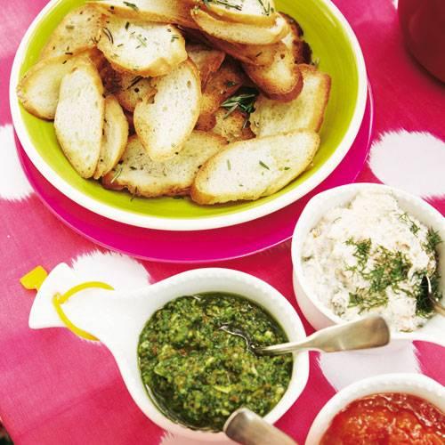 Sie haben die Qual der Wahl: Zu den Baguette-Chips gibt's Lachs-, Rauke- und Paprika-Basilikum-Dip. Zum Rezept: Baguette-Chips mit Dips