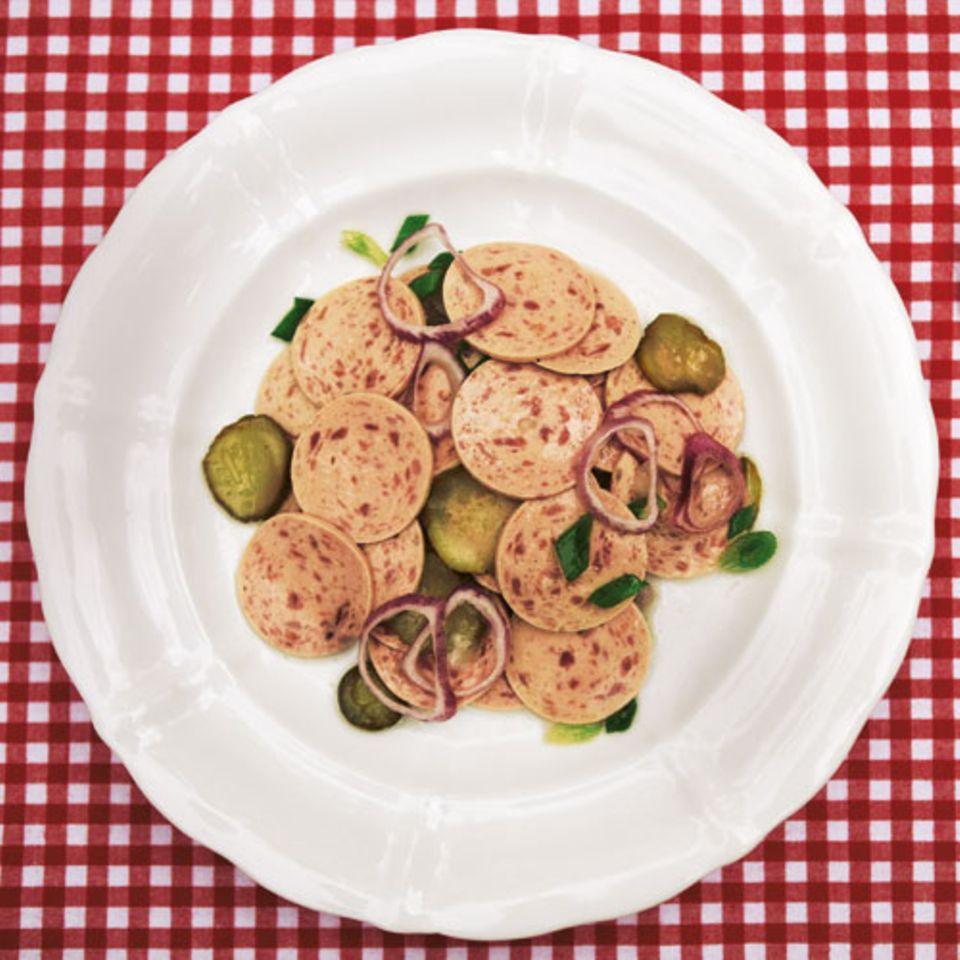 Wurstsalat ist Vertrauenssache - beim Fleischer landen oft genug die wenig ansehnlichen Reste der gesamten Woche drin. Also: lieber selber machen - mit Regensburgern, Zwiebeln, Gurken. Zum Rezept: Wurstsalat