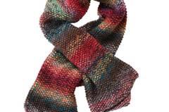 Das Garn aus Wolle und Seide ist mit vierfachem Faden gestrickt - so wird ein herrlich dicker und bunter Schal daraus. Zur Strickanleitung: Perlmusterschal stricken