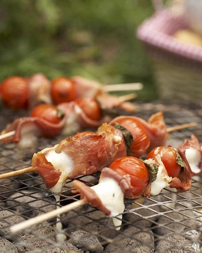 Fingerfood vom Grill: einfach Mini-Mozzarellas, Kirschtomaten, Serrano-Schinken und Salbei abwechselnd aufspießen, grillen - und direkt vom Spieß knabbern. Zum Rezept: Tomaten-Saltimbocca-Spieße