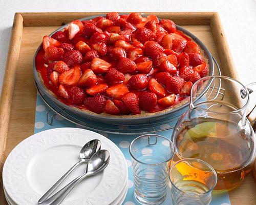 Zwei Gründe, warum ausgerechnet dieser ganz schlichte Erdbeerkuchen auf einem Buffet mit lauter raffinierten Sahnetorten als erstes aufgegessen ist: Mehr Erdbeeren geht nicht - mehr Sommer auch nicht. Zum Rezept: Pudding-Tarte mit Erdbeeren