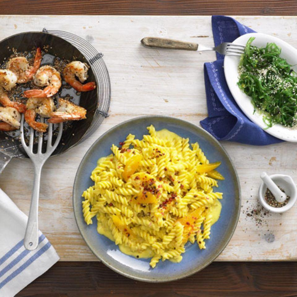 Nur glückliche Gesichter: Die Fusilli mit Orangen-Safransoße verfeinern Sie je nach Geschmack mit Garnelen mit gebratenem Sesam oder mit grünem Algensalat mit Sesam. Wenn Sie alles hübsch der Reihe nach fertig machen, gibt's keinen Stress. Beginnen Sie am besten mit der Zubereitung der Basis-Soße für alle. Für die richtige Konsistenz: Wenn die Soße zu dick ist, später mit Pasta-Wasser verdünnen. Ist die Soße zu dünn, ein wenig länger köcheln lassen - so lange, bis ausreichend Flüssigkeit verdampft ist. Zum Rezept: Fusilli mit Orangen-Safransoße