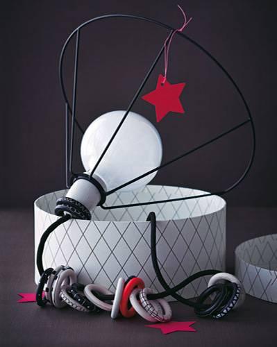 Lampengestell (in Schwarz) und Gardinenringe ansprühen. Nach dem Trocknen die Ringe von Hand mit Strichen, Linien und Punkten bemalen und aufs Kabel fädeln.