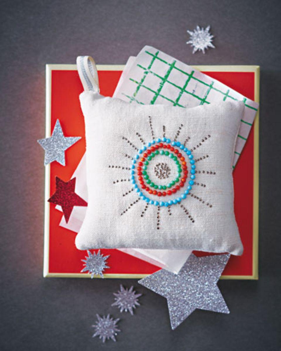 Aus dem Stoffrest zwei Quadrate à 13 x 13 cm ausschneiden und auf links zusammennähen, eine ca. 5 cm große Öffnung lassen. Kissen wenden, mit Stopfwatte ausstopfen und zusammennähen, dabei den Aufhänger aus Deko-Band mit einnähen. Zum Schluss die Stecknadeln so ins Kissen piksen, dass sie ein Muster ergeben.