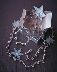 Von ca. 2 m Stickgarn (meist ist es 6-fädig) zwei Fäden abtrennen. Dann ca. 400 Perlen auf einen der beiden Fäden auffädeln (man kann später bei Bedarf auch noch weitere Perlen nachfädeln). Jetzt mit der Häkelnadel aus beiden Fäden zusammen 16 Luftmaschen häkeln, dabei den Anfangsfaden zum späteren Nähen für die Verschluss-Öse lang lassen. Nun fünf Perlen ranholen und mit der nächsten Luftmasche straff mithäkeln. Acht Luftmaschen ohne Perlen häkeln, dann wieder eine Luftmasche mit fünf Perlen, gefolgt von acht Luftmaschen ohne häkeln usw. So oft wiederholen, bis die Kette die gewünschte Länge hat (in unserem Beispiel sind es 80 Perlen-Luftmaschen, das ergibt eine 100 cm lange Kette). Zum Abschluss ca. 15 Luftmaschen häkeln, daraus eine Kugel formen, indem man die Luftmaschen zusammenzieht und immer wieder durch eine Luftmasche verbindet. Die Kugel soll so groß sein, dass sie gut hält, wenn man sie durch die Öse schiebt. Diese entsteht, indem man die Luftmaschen vom Anfang zur Schlaufe zusammennäht.