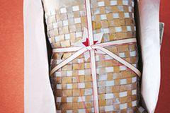 """Goldenes Leder in zwei Teile à 27 x 48 cm bzw. 27 x 36 cm schneiden. Ins größere Stück mit einer scharfen Schere beginnend von der einen kurzen Seite 1 cm breite und 30 cm lange Fransen schneiden. Graues Leder in 1 cm breite und 27 cm lange Streifen schneiden, diese in die goldenen einweben, dabei an den Seiten mit Kleber verkleben, um die Streifen zu fixieren. Bis zum Ende durchweben. Das 27 x 36 cm große goldene Lederstück bildet zusammen mit dem überstehenden ungeflochtenen Teil des Vorderteils die Kissen-Rückseite. Teile rechts auf rechts legen, das überstehende Stück der Vorderseite nach außen umklappen (das wird der """"Hotelverschluss""""), das Ganze an den anderen drei Seiten so zusammensteppen, dass eine 25 x 40 cm große Hülle entsteht. Auf rechts drehen, Inlay einschieben."""