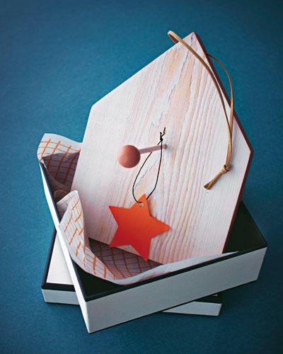 Brett in Haus-Form zuschneiden lassen. Flächen weiß lasieren, Seitenkanten farbig anmalen. Mittig ein Loch für den Rundstab und quer durch die Dachspitze ein Loch für die Aufhängung bohren. Lederband einfädeln, Rundstab für den Meisenknödel festleimen, Holzperle aufstecken.