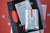 Für die Handy-Hülle: Handy auf die Innenseite des Leders legen, mit einem Stift umfahren und die Silhouette mit ca. 1 cm Zugabe (abängig von der Dicke des Handys) mit dem Cutter ausschneiden und Ecken abrunden. Dieses Stück als Schablone für ein zweites Stück verwenden. Außerdem einen Lederstreifen (ca. 1 x 15,5 cm) zuschneiden. Nun in die beiden großen Stücke mittig und mit ca. 1 cm Abstand zwei 1,2 cm lange, waagerechte Schlitze schneiden. Die beiden großen Lederstücke an drei Rändern mit Kleber aufeinanderkleben, antrocknen lassen, mit der Nähmaschine und einer Ledernadel zusammensteppen. Jetzt das Gummiband vom Taschenkalender abschneiden und mit der Maschine an das eine Ende des Lederstreifens steppen. Durch die Schlitz-Lasche ziehen und mit einem Stift anzeichnen, wo die Sterne des Punzeisens platziert werden. Das Lederband wieder rausziehen, auf ein Reststück Leder legen und mit Hammer und Punzeisen die Sterne durchschlagen (vorher unbedingt einen Probestern ausstanzen!). Jetzt das Lederband durch beide Laschen ziehen und das Gummiband mit der Nähmaschine daran feststeppen. Das Gummiband kann zusätzlich mit einem Faden an der oberen Lasche festgesteppt werden, damit das Band an der Tasche fixiert ist. Für den Kalender: Aufgeschlagenen Kalender als Schablone auf die Innenseite des Leders legen, mit einem Stift umfahren und das Leder mit einer Zugabe von 4 mm in der Höhe und 6 cm in der Länge zuschneiden. Kalender in das Leder einschlagen und es auf beiden Seiten 3 cm umschlagen. Umschläge an den Rändern mit etwas Klebstoff fixieren, mit einer Lederahle kleine Löcher vorstechen, mit Knopflochgarn den Umschlag festnähen und zum Schluss den Faden gut vernähen. Den Kalender in den Ledereinband einschlagen und schauen, ob er passt. Dann mit einem dünnen Stift die gewünschte Position der Sterne markieren, den Einband abziehen und die Sterne mit dem Punzeisen und einem Hammer durchschlagen.