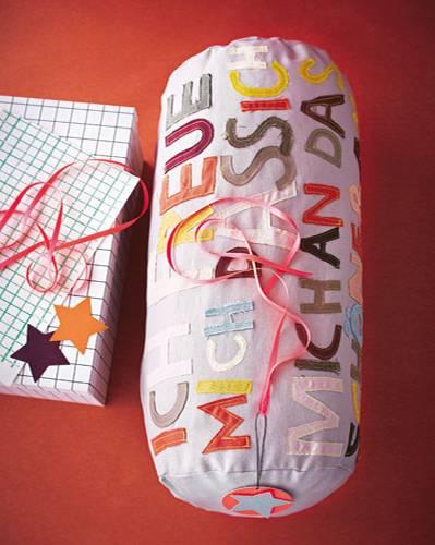 Gedicht oder Zitat auswählen, aus Stoffresten die Buchstaben ausschneiden und unversäubert mit der Maschine auf den Kissenbezug steppen.