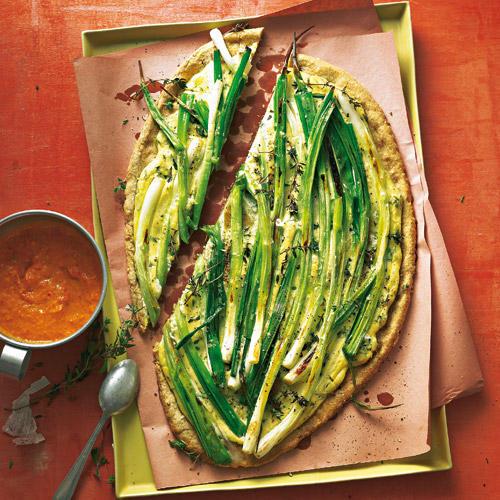 Auf den knusprigen Mürbteigboden mit Braunhirse kommen Tofucreme, Thymian und Lauchzwiebeln. Der schön scharfe Clou dazu: die spanische Salsa mit feiner Mandelnote. Rezept: Lauchzwiebel-Tarte mit Salsa Romesco